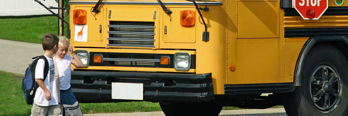 A school bus dropping off students. Become certified through TAPTCO's bus driver training program.